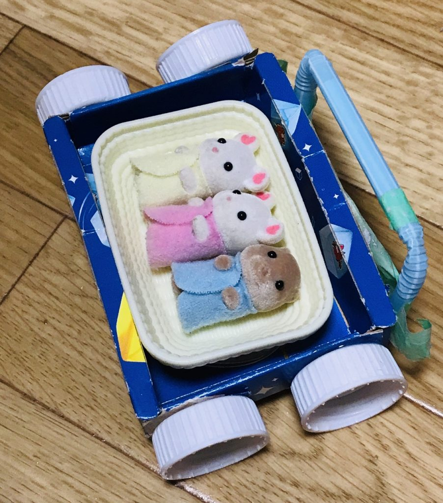 ベルキューブの空き箱とR1のペットボトルの蓋で作ったベビーカーに赤ちゃんが寝ている様子